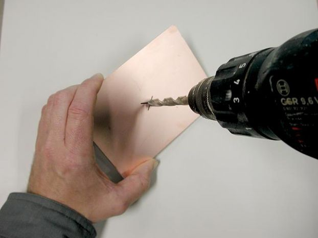 Просверлите отверстие диаметром на пару миллиметров больше диаметра кабеля